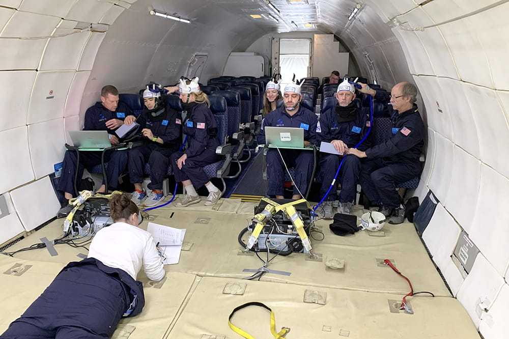 the team sits in seats inside an otherwise empty plane with stark white walls. One team member lays on her stomach in front of the group looking at a laptop
