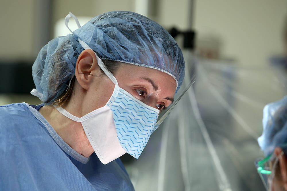 Dr. Heather Evans wearing a surgical cap and mask.