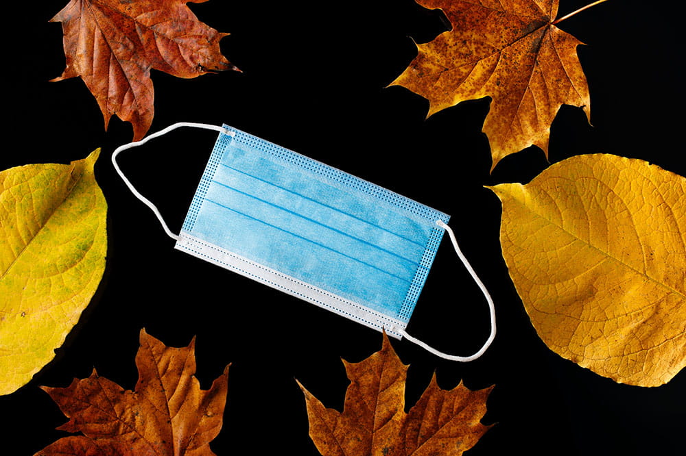 Surgical mask on a black background surrounded by autumn leaves