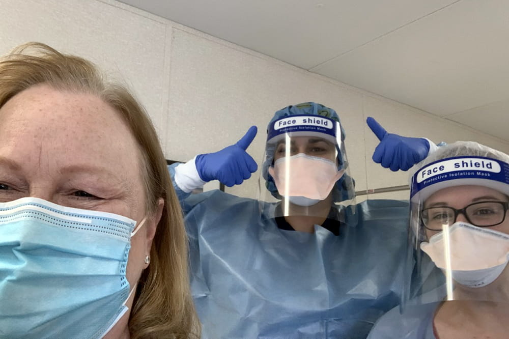 Three women post for a selfie. The patient wearing a mask and the nurses wearing gowns, gloves, masks and face shields. One nurse gives two thumbs up.