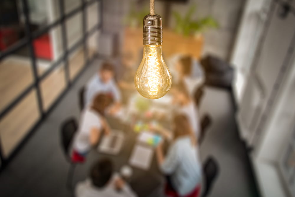 A lightbulb superimposed upon a conference room with people meeting to discuss ideas. Licensed from istock.com