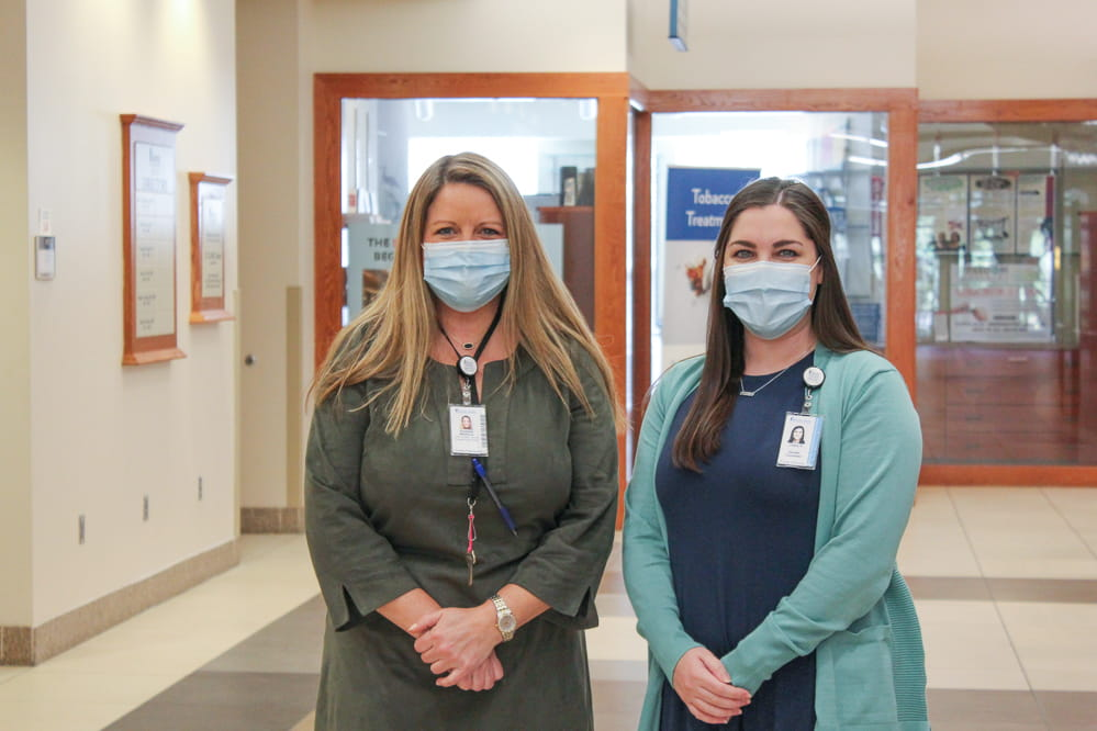 Genetic counselors Libby Malphrus (left) and Charly Harris pose for a photo in the main hallway of MUSC Hollings Cancer Center March 17, 2021. Photo by Kelsey Hudnall