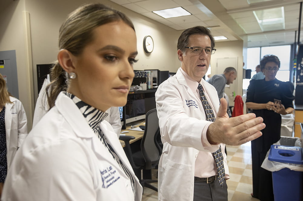 Miss America listens as researcher Chip Norris speaks and gestures