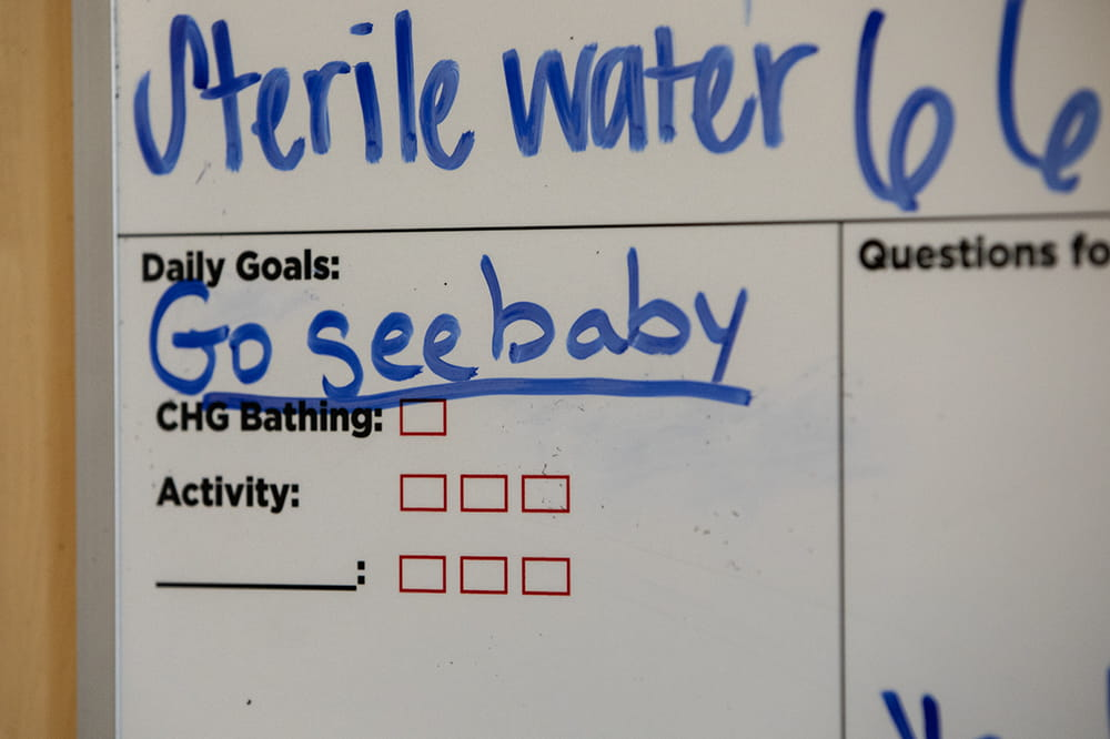 Whiteboard with the words Go see baby as a daily goal.