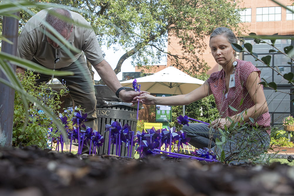 a man and a woman place purple mills in a flower bed