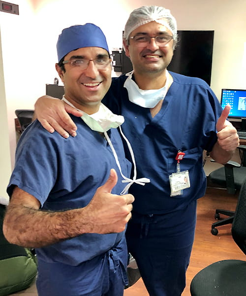 two surgeons give a thumbs up smiling broadly