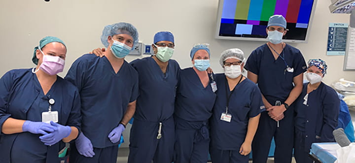 a group of people in dark blue scrubs and operating room caps pose